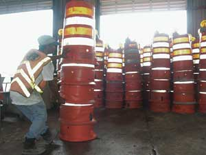 Eddie S. Ortiz drags traffic barrels for  re-installation after Hurricane Frances blew through West Palm Beach. The barrels had to be packed away again just three weeks later for Hurricane Jeanne.