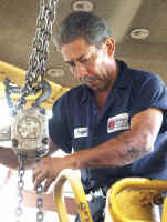 Angel Berrios uses a hand winch to position a torque convertor while working on a D6 Dozer at Ranger North's maintenance shop.