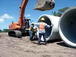 "One of Ranger's new pipe crews includes Hoe Operator James ""Lee"" Lucas and Pipe Layers Bruce Morgan, Byron Walker and Tommy Walker, shown getting ready to install 72"" drainage pipe at Botanica, a site development project in Jupiter, Florida. Foreman Brian Kennedy and Pipe Layer Juan Bravo not shown."