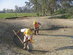 Ranger Golf workers sculpt the edges of a sand bunker at Dos Lagos.
