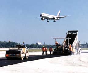 A Ranger paving crew lays a lift of asphalt on a PBIA taxiway, while an airplane comes in for a landing on the nearby runway.