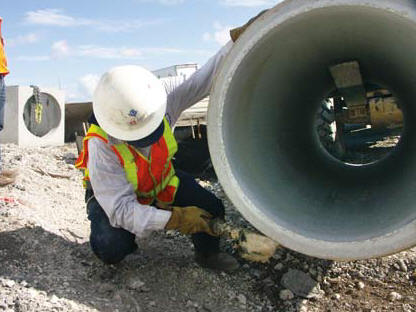 Above: Ranger Hoe Operator Bobby Richard applies sealant to a drainage pipe on a road construction and asphalt paving project on I-595 in Ft. Lauderdale, FL. (Photo by Carl Thiemann)