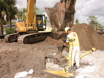 Domingo Reyes chains a compacting machine to an excavator bucket so Hoe Operator Gonzalo Arango can move it into position on Ranger Central's 25th Street project. (Photo by Carl Thiemann)