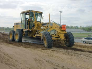 Grader Operator John Hughes shapes the dirt as it approaches one of the roadway's many bridges. (Photo by Carl Thiemann)