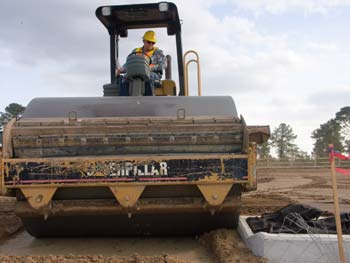 Roller Operator Mike Richards compacts the dirt to eliminate excessive voids, or tiny air pockets, ensuring that the road base has the stability and strength needed to support traffic. (Photo by Carl Thiemann)