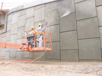 Ray Rueda pressure cleans one of 23 mechanically stabilized earth (MSE) walls on Ranger's SR-414 project prior to painting, as George Ignatius works the lift controls. (Photo by Carl Thiemann)