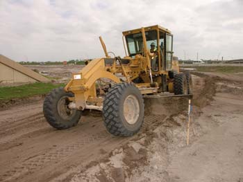 Grader Operator David Thomas shapes a new entrance ramp. (Photo by Carl Thiemann)