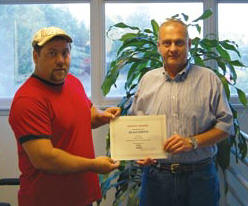 "Sharpe V.P. Ivan Clayton, right, presents Sean Smith with a 2012 Safety Phrase award for his entry: ""SAFETY: We're All Riding On it!"" Runner-up was Rob Williams of V&G. (Photo by John Riley, Jr.)"